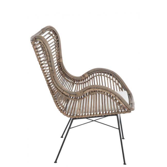 Chaise en rotin naturel avec coussin blanc et pieds en métal noir.